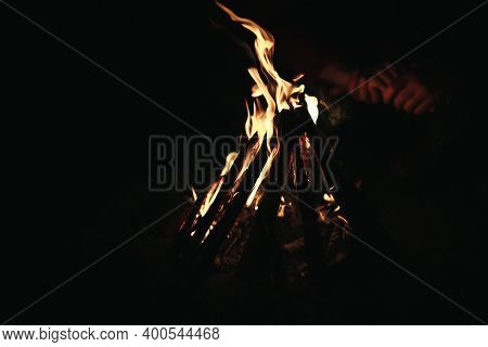 Couple In Love Holding Hands By Burning Firewood At Night. Bonfire In A Tourist Camp On The Nature I