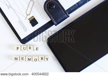 Pure Memory Lettering Next To An Open Blank Notebook, Micro-sd Memory Card, Smartphone And Ejector F