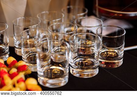 Glasses With Cognac, Whiskey Stand On The Bar. A Lot Of Glasses With Cognac. Alcohol In The Glasses.