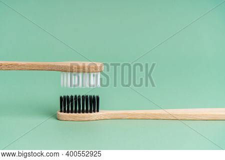 Two Eco-friendly Antibacterial Bamboo Wood Toothbrushes With White And Black Bristles On A Light Gre