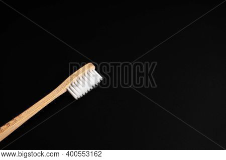 Eco-friendly Antibacterial Bamboo Wood Toothbrush With White Bristles On A Black Background. Taking