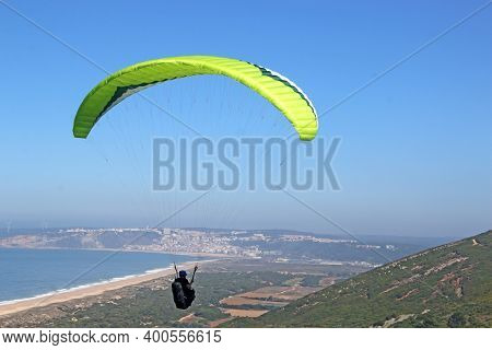 Yellow Paraglider Above Salgado Beach In Portugal