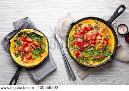 Healthy Frittata In Two Cast Iron Pans With Fried Beaten Eggs And Seasonal Vegetables On Rustic Wood