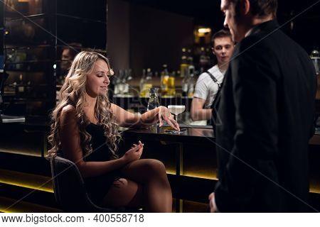 Cute Blonde Flirts With A Man In A Jacket In A Nightclub.