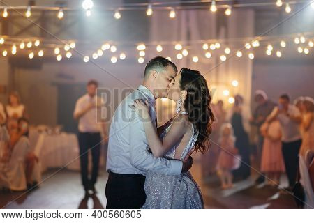 Bride And Groom Kissing In The Restaurant At The Wedding. Happy Newlyweds At The Wedding Party