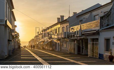 People Enjoying An Evening Walk On The Rua Vasco Da Gama In Porto Covo In Golden Evening Light
