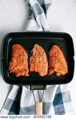 Marinated Turkey Steak With In A Black Grill Pan On The Table. High Quality Photo