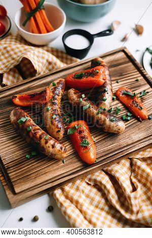 Grilled Sausages And Bell Peppers On A Wooden Board. High Quality Photo