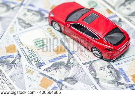 Red Toy Car Is Standing On Dollar Banknotes. Cost Of Buying A Car, Fuel, Insurance And Other Car Cos