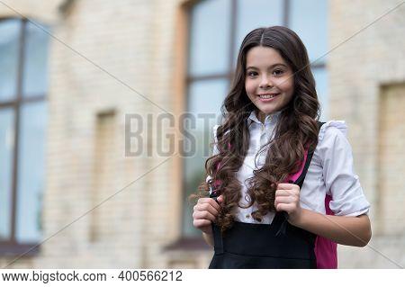Happy Kid Wear Long Wavy Hair With Back To School Look In Schoolyard, Salon, Copy Space.