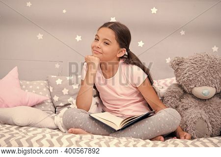 Literature Hobby. Dreaming Big. Girl Child In Bed Read Book With Teddy Bear Plush Toy. Pleasant Time