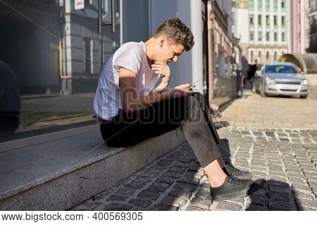 Boy Teenager 16, 17 Years Old, Using Smartphone, Sitting On Street Of Summer City, Guy Reads An Onli