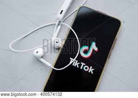 Tver, Russia-february 12, 2020 Tik Tok Logo On The Smartphone Screen And White Wireless Headphones O