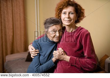 Elderly Old Cute Woman With Alzheimers Very Happy And Smiling When Eldest Daughter Hugs And Takes Ca
