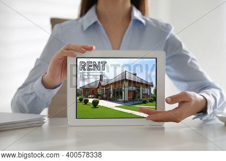 Woman Showing Rental Property Website On Tablet Computer, Closeup