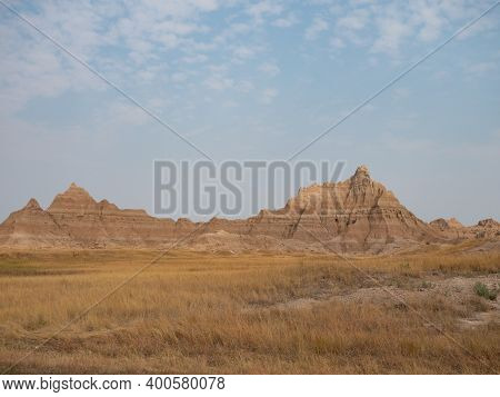 Rugged, Striated Mountains With A Prairie And Dried Grass In The Foreground And Thin Clouds Above. B