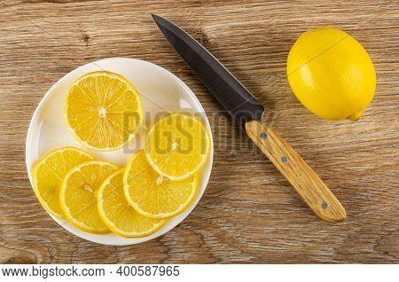 Half Of Lemon, Few Slices Of Lemon In Glass White Saucer, Kitchen Knife, Whole Lemon On Brown Wooden