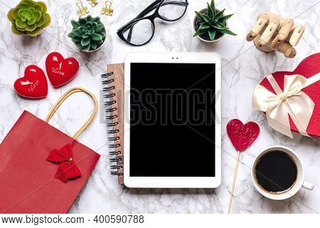 Tablet For Chooses Gifts, Makes Purchase, Cup Of Coffee, Debit Card, Box, Bag, Two Hearts On Marble