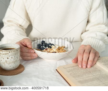 Reading Book And Eating Healthy Holiday Winter Breakfast With Granola Muesli And Yogurt In Bowl On W
