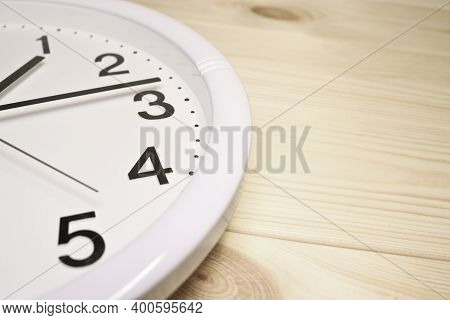 Dial Of Analog Clock Close-up On A Wooden Background. The Time Is 13:14. White Dial, Black Numerals.