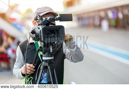 Video Camera Operator Working With His Equipment. Video Cinema Production. Covering An Event With A