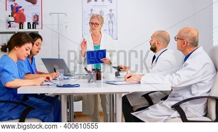 Portrait Of Mature Woman Doctor Heading Committee Meeting At Medical Council Presenting New Medical
