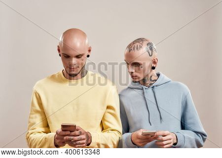 Two Young Caucasian Twin Brothers In Casual Wear With Tattoos And Piercings Using Smartphones While