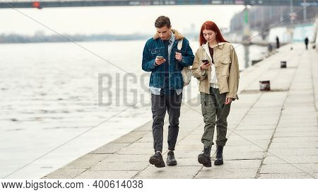 Full Length Shot Of Two Teenagers Totally Absorbed In Their Smartphones, Ignoring Each Other While W