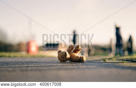 Lost Teddy Bear With Sad Face Lying On Footpath With Blurry People Background,lonely Bear Doll Layin