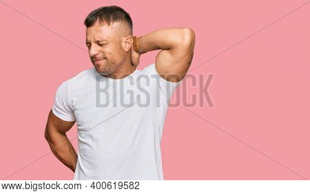 Handsome muscle man wearing casual white tshirt suffering of neck ache injury, touching neck with hand, muscular pain