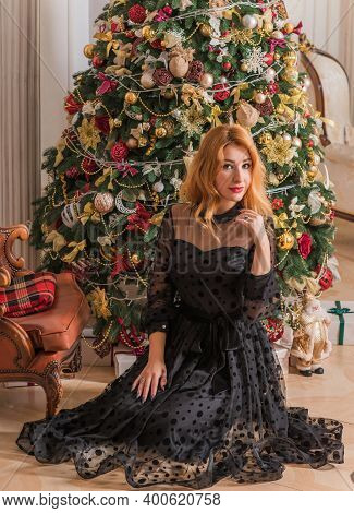 Christmas Cozy Atmosphere At Home. Elegant Woman Near Christmas Tree In Elegant Interior, Holly Chri