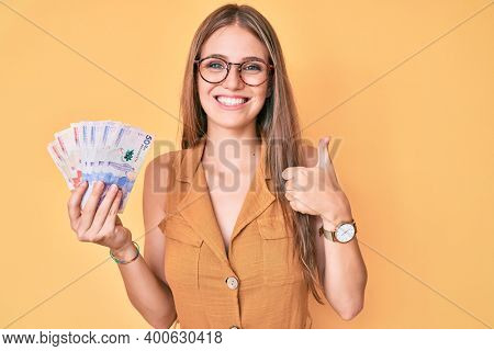 Young blonde girl holding colombian pesos smiling happy and positive, thumb up doing excellent and approval sign
