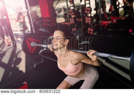 Athletic Girl In Sportswear Performs Exercises With Barbell, Dumbbells. Fitness, Healthy Lifestyle