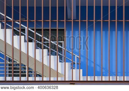 Fire Escape With Protective Balusters Outside Of Blue Facade