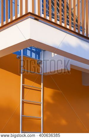 Low Angle View Of Fire Escape With Safety Baluster On Colorful Building Wall In Vertical Frame