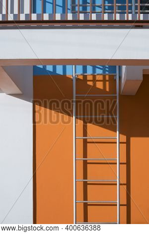 Sunlight And Shadow On Fire Escape Surface With Safety Baluster On Colorful Building Wall In Vertica