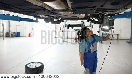Young African American Girl In Car Service Station Uniform With Flashlight Inspecting Car Bottom Ins