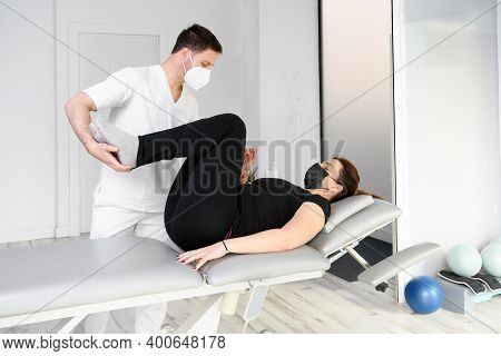 Physiotherapist With Protective Mask Giving A Massage To A Patient. Reopening With Physiotherapy Saf
