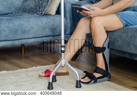 The Woman With A Orthotics On Her Foot Is Sitting On The Sofa At Home
