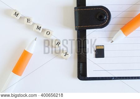 Micro-sd Memory Card Next To An Open Notebook And A Fountain Pen. Comparison Of Modern Memory Storag