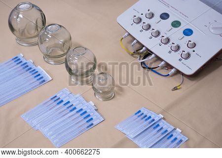 Medical Cupping Glass And Various Needles With Nerve And Muscle Stimulator On Tablecloth For Acupunc