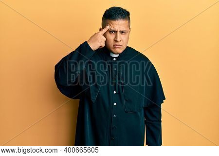 Young latin priest man standing over yellow background pointing unhappy to pimple on forehead, ugly infection of blackhead. acne and skin problem