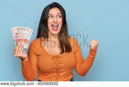 Beautiful hispanic woman holding 10 colombian pesos banknotes pointing thumb up to the side smiling happy with open mouth