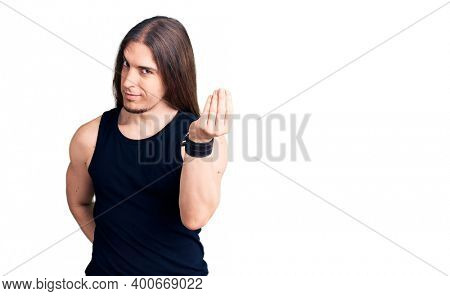 Young adult man with long hair wearing goth style with black clothes doing italian gesture with hand and fingers confident expression