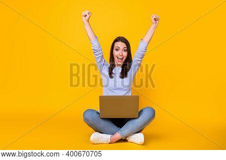 Full Length Photo Of Crazy Ecstatic Girl Sit Floor Legs Crossed Work Remote Laptop Raise Fists Screa