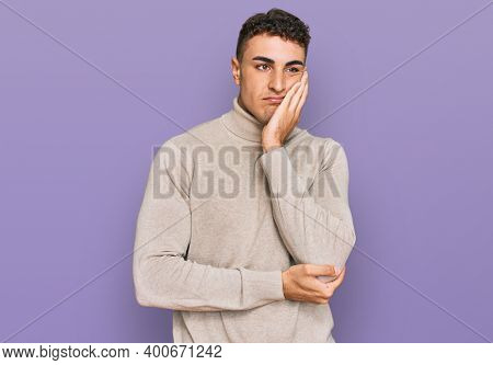 Hispanic young man wearing casual turtleneck sweater thinking looking tired and bored with depression problems with crossed arms.