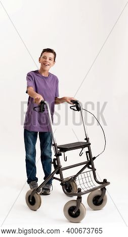 Full Length Shot Of Happy Teenaged Disabled Boy With Cerebral Palsy Smiling At Camera, Taking Steps
