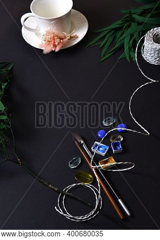 The Background Is Black With A Cup On A Saucer, Eucalyptus Leaves, Rope, Watercolor Paints, Brushes.
