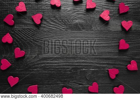 Frame Of Purple Hearts On Black Wooden Background