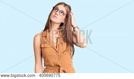 Young beautiful blonde woman wearing casual clothes and glasses confuse and wondering about question. uncertain with doubt, thinking with hand on head. pensive concept.